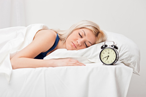 Woman Sleeping Next to Alarm Clock